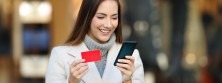 Happy woman smiling at phone and holding credit card